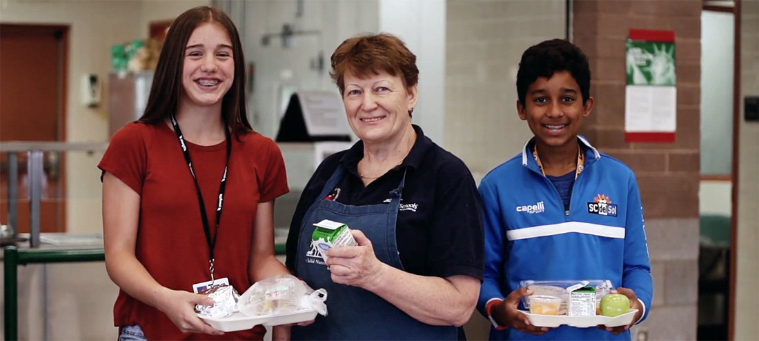 Nutritional Services Worker Smiles Next To Two Students With Lunch Trays