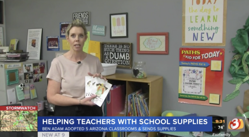 Teacher holding school supplies